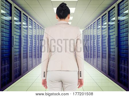 Digital composite of Business woman back view standing in a corridor