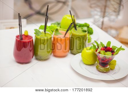 Red and green healthy smoothies with fresh ingredients on table