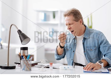 Take care of yourself. Sick male wearing casual clothes, wrinkling his forehead putting left hand on the table