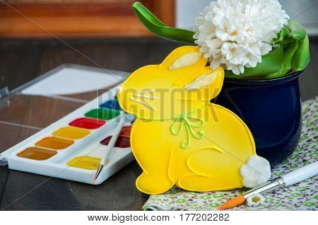Decorated Easter Bunny Cookie Chamomiles Hyacinth in a jar Paints and Brushes on a wooden background. Easter concept.