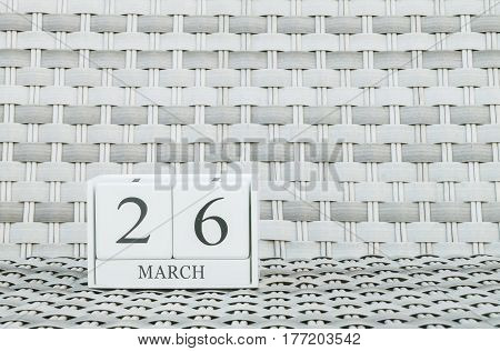 Closeup surface white wooden calendar with black 26 march word on blurred weave wood chair textured background with copy space selective focus at the calendar