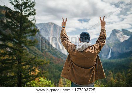 man in winter coat cheering infront of yosemite