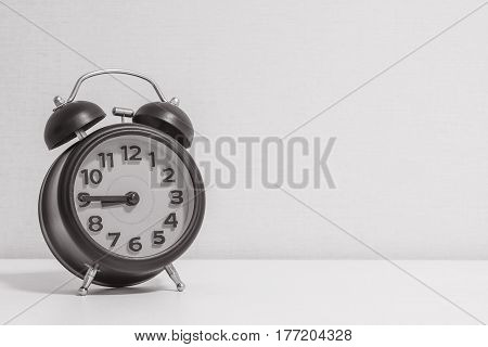 Closeup alarm clock for decorate show a quarter to nine p.m. or 8:45 a.m. on white wood desk and cream wallpaper textured background in black and white tone with copy space