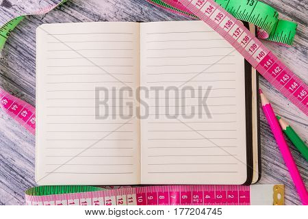 Diet Plan. Healthy Lifestyle Concept. Nutrition Journal Near Measuring Tape And Pink And Green Penci