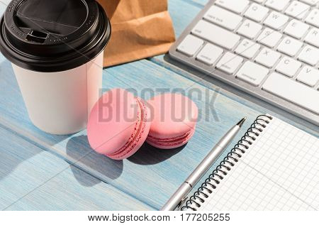 Working on the go. White modern keyboard with coffee cup, candies and notepad on blue wooden table at sunny weather