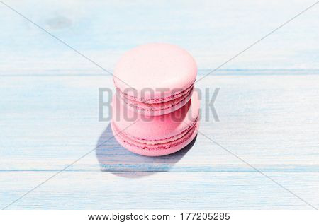 Two pink macaroons on blue wooden table