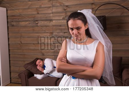 Unhappy bride, sleeping groom on background