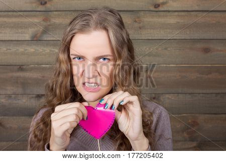 Girl with angry face holding pink heart on a stick