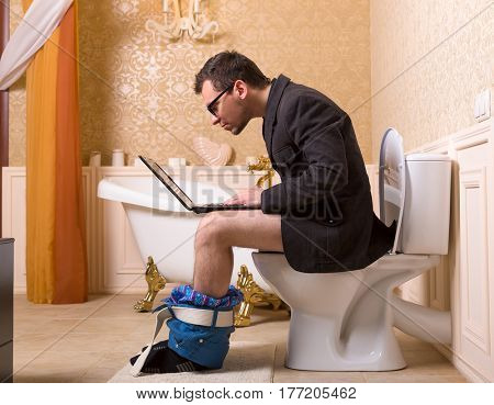 Man in glasses with laptop sitting on toilet bowl