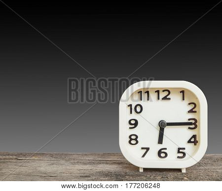 Closeup white clock for decorate show a quarter past six or 6:15 a.m. on old brown wood desk isolated on black background with copy space
