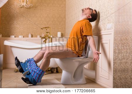 Man with pants down sitting on the toilet bowl