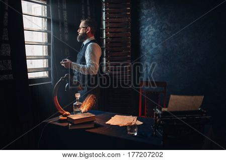 Bearded writer in glasses smoking a cigarette