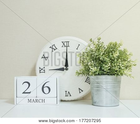 White wooden calendar with black 26 march word with clock and plant on white wood desk and cream wallpaper textured background selective focus at the calendar