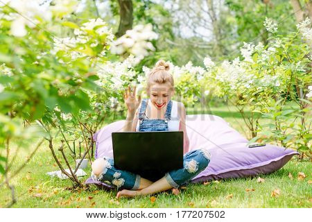 Happy freelancer working in the garden. Writing, surfing in the internet. Young woman relaxing and having fun in park area waving to the camera during a video call. Distance education, freelance concept