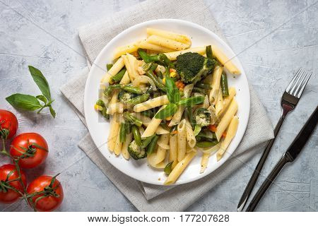 Italian vegetarian pasta penne with green vegetables. Top view copy space. Portion plate.