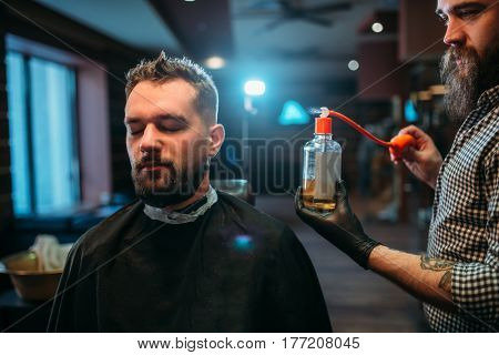 Barber splashing client face by aftershave lotion