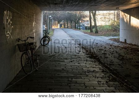 View through a tunnel. In the tunnel is parked bicycles and after the tunnel shows a tree-lined avenue and there can be glimpsed buildings