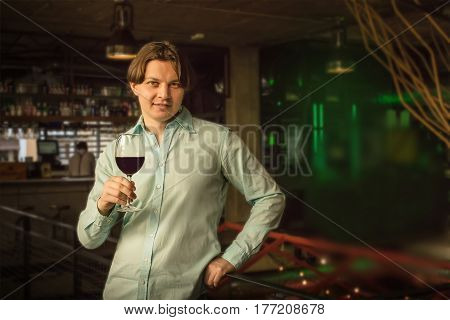 A photo of a man with a glass of wine against a blurred background of a bar, with a place for text