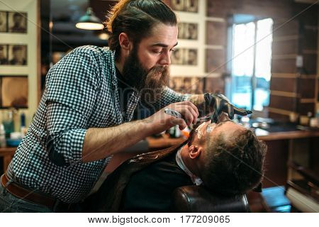 Barber shaves beard of the client by shaving blade