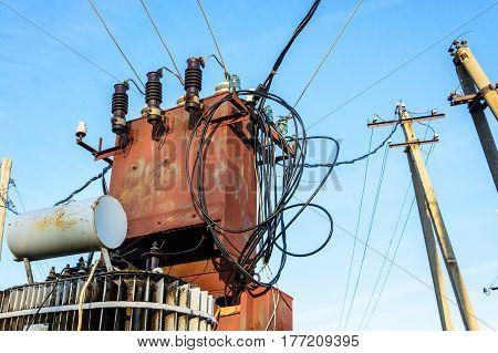 Old red electric transformer substation on blue sky background.