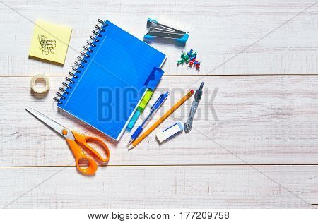 View of a wooden table with a notebook, pen, pencil, rubber, scissors, sellotape, calipers, stapler and pins