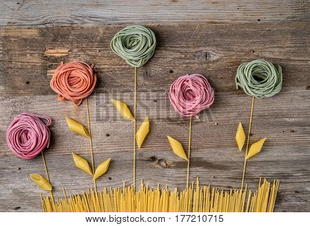 flowers composition made out of colorful pasta on the dark wooden table, topview