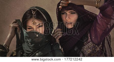 Travel concept. Adventure of two sisters princesses in the desert. Two girls have got to a sandstorm during journey. Creative art fashion portrait shot of two gorgeous attractive models with luxury make-up and hairstyle outdoors. Sand effect not noise.