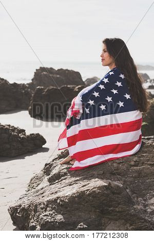 woman with american flag at the beach.