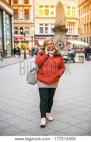 A nice middle age woman walking on the shopping street in a winter jacket while talking on the phone