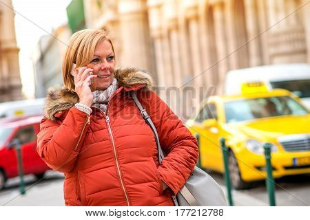 A nice middle age woman standing and wanting for her taxi while talking on the phone