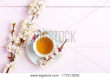 Cup of  tea and spring  flowers  on  light pink  wooden table.