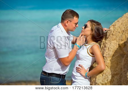 Couple in love flirts on the beach. The guy holds the girl by a chin and attracts to himself.
