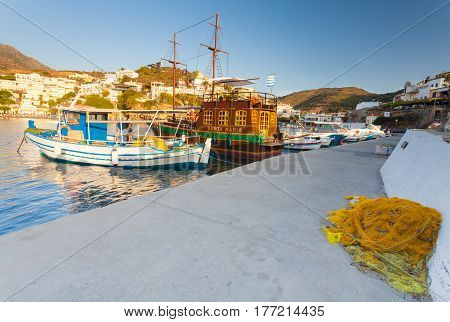 Bali Island Crete Greece - June 24 2016: Beautiful morning scenery with village Bali bay of Mediterranean sea and boats of local fishermen and and the big old wooden ship for walking tourists in the sea. Yellow net for catching fish is dried on the pier