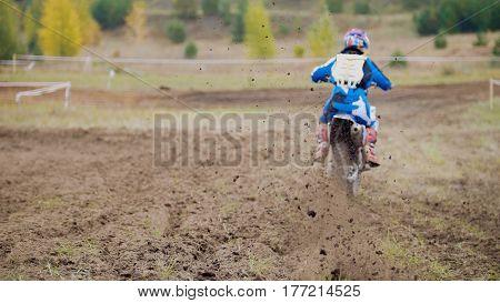 Motocross racer starting on dirt Cross MX bike - pieces of dirt flying - de-focused, telephoto