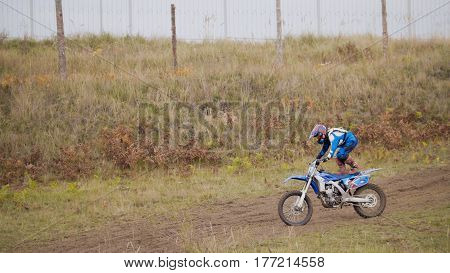 MX moto Girl Biker shows acrobatic at cross racing - rider on a dirt motorcycle, telephoto