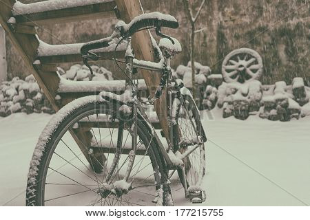 Vintage bike in the winter in the snow chained to a wooden ladder against the wall with a cart wheel