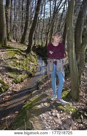 Girl stands with crossed arms in the brook in the wood, with sad expression