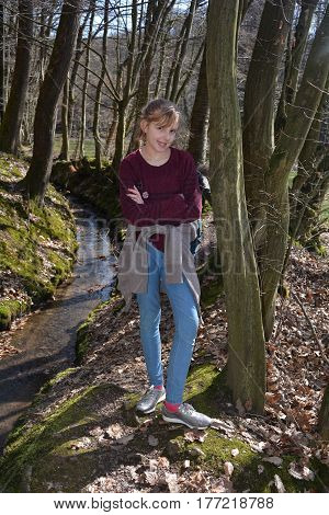 Girl stands with crossed arms in the brook in the wood and smiles forwards