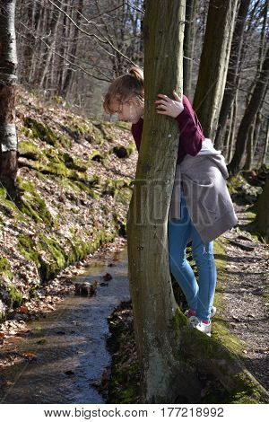 Girl in the tree looks in the brook