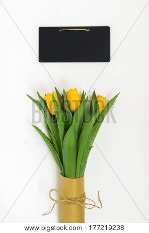Bouquet Of Yellow Tulips Packed In Kraft Paper In Retro Style And Chalky Writing Board Isolated On W