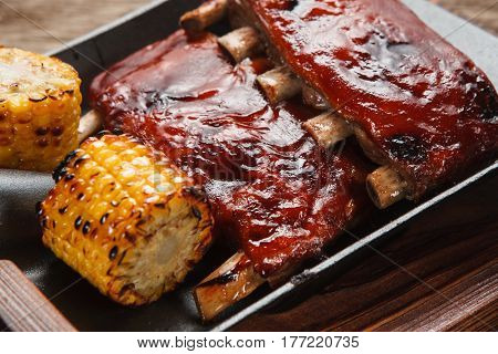 American delicious food. Appetizing grilled pork ribs with corn served on shovel, close up view. Junk food, picnic, bbq concept