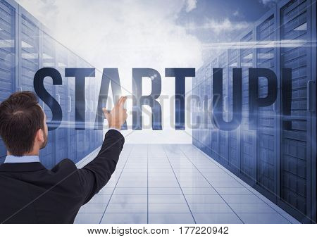 Digital composite of Businessman Standing pointing at Start Up Word against a blue background