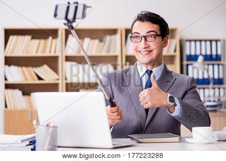 Funny businessman taking selfie in office