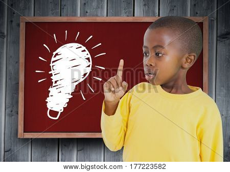 Digital composite of kid and blackboard with lightbulb against a wood background
