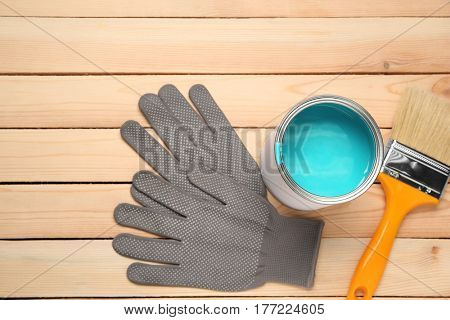 Paint can, gloves and brush on wooden background