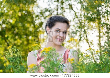 Positive girl in nature near a tansy