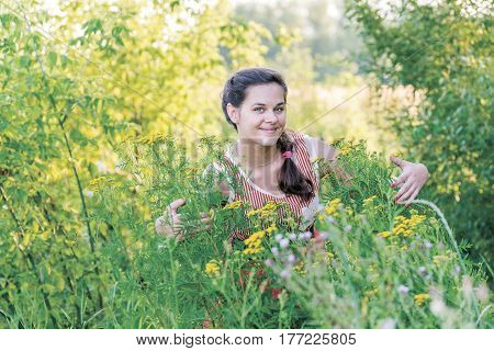 Smiling girl is hugs a tansy outdoors