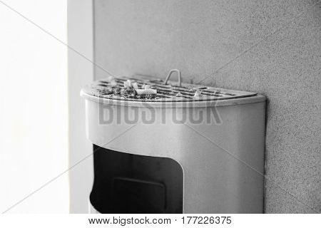 Trash bin with cigarettes butts, indoor