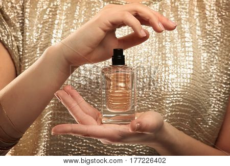 Beautiful young woman with bottle of perfume, closeup