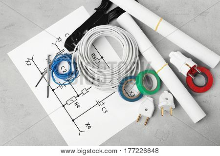 Electrician tools and scheme on grey background